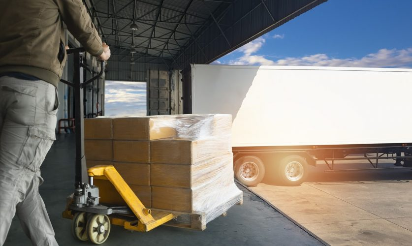 Worker courier unloading cargoshipment pallet goods, package box, his using hand pallet jack load into a truck, Road freight transport, Warehouse industrial delivery shipment and logistics